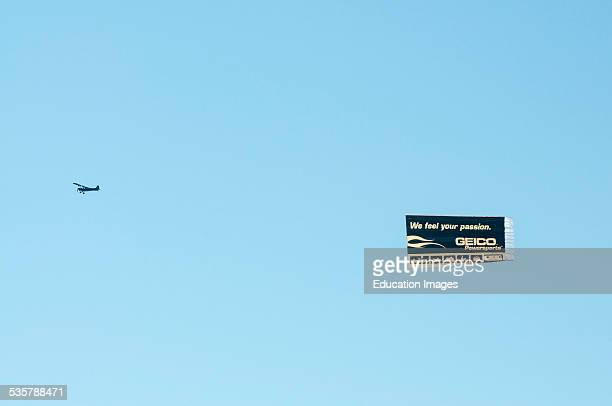 Small airplane towing an advertising banner for GEICO Power sports insurance on race day near the Kansas Speedway