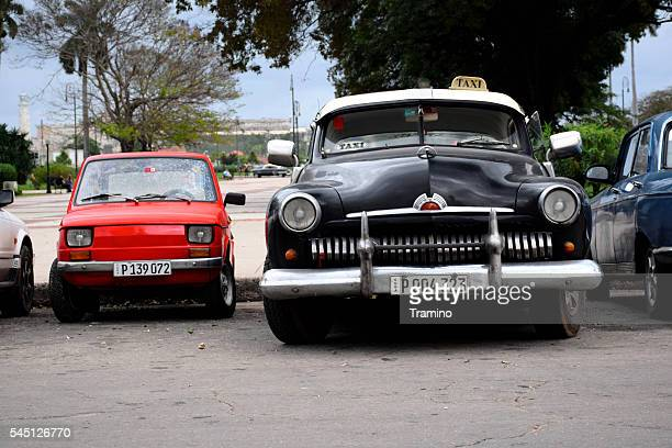 Small and large classic vehicle on the street in Havana