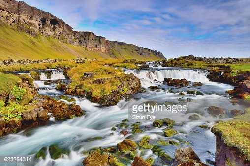 Small and rapid cascade with a mountain in the background in southern Iceland