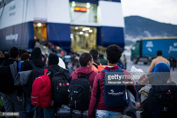 A small baby cries while Migrants and refugees mainly from Afghanistan and Syria line up at the port of Mytelene to board a ferry to Athens on March...