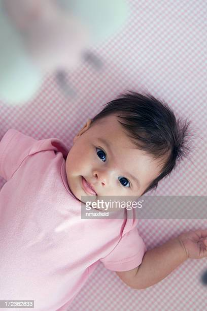 A small baby in a crib with a mobile, wearing a pink onesie