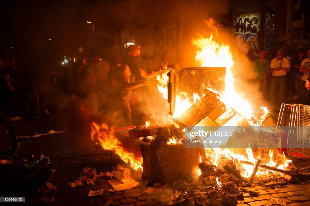 TOPSHOT - A small barracade is burning in front of the Rote Flora left-wing centre after the 'Welcome to Hell' rally against the G20 summit in Hamburg, northern Germany on July 6, 2017. Leaders of the world's top economies will gather from July 7 to 8, 2017 in Germany for likely the stormiest G20 summit in years, with disagreements ranging from wars to climate change and global trade. /