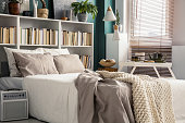 Creative use of small space in a stylish bedroom interior with designer decor and cozy white and beige bedding