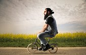 Bearded man is sitting on a small bicycle