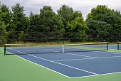 A small, blue asphalt neighborhood tennis court surrounded by green