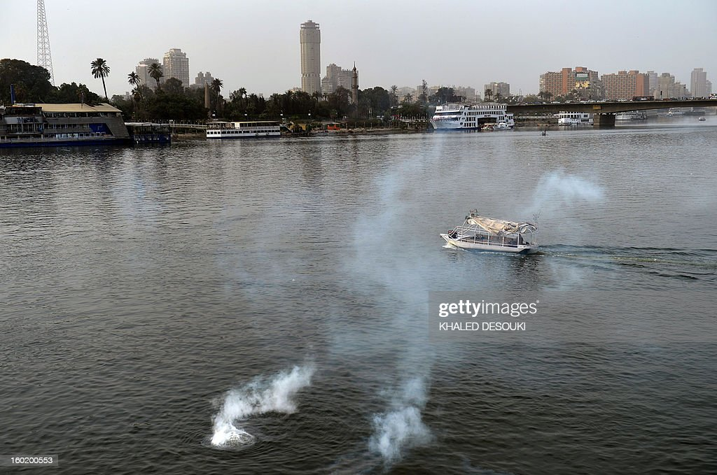 A small boat cross the river Nile as tear gas canisters fired by Egyptian riot police land in the water during clashes near Cairo's Tahrir Square, on January 27, 2013. Clashes killed at least 31 people in Egypt's Port Said as violence raged into the early hours in several cities including the capital following death sentences passed on 21 football fans after a riot.