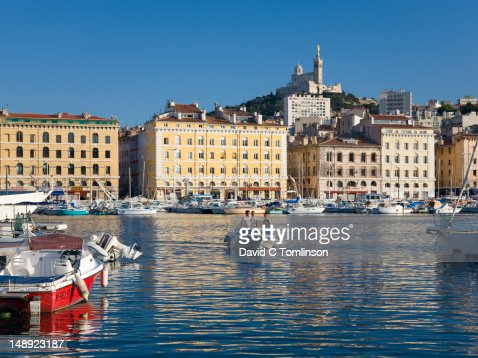 Small boat crossing Vieux Port with Basilique de Notre Dame de la Garde on hilltop in background.