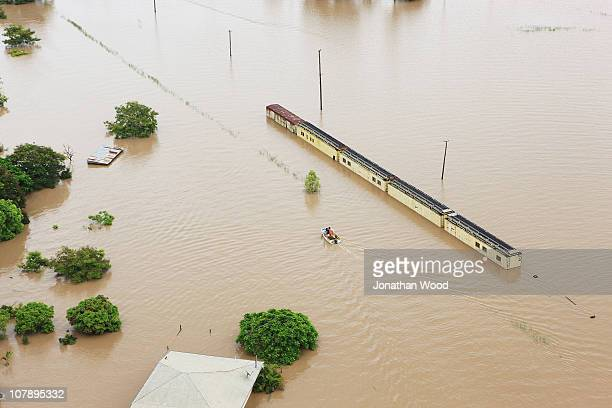 A small boat cruises past a train submerged by flood water on January 6 2011 in Rockhampton Australia Floodwaters peaked at 92 metres yesterday in...