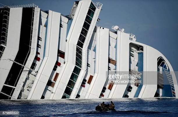 A small boat moves towards the stricken cruise liner Costa Concordia off the Isola del Giglio on January 21 2012 The head of the search operation at...