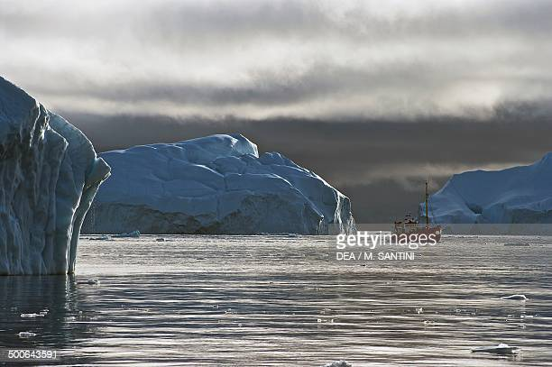 A small boat near the iceberg detached from Jakobshavn glacier Ilulissat village Qaasuitsup west Greenland Denmark