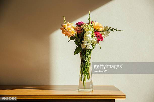 Small bouquet of summer flowers on old wooden sideboard