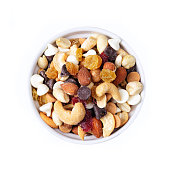 Small bowl of trail mix, including peanuts, almonts, cashews, dried cranberries, yellow raisins, chocolate chips, white chocolate chips, isolated on white