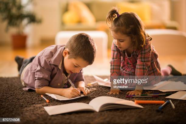 Small boy and girl drawing on a carpet at home.