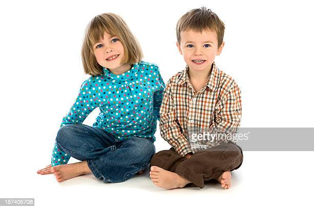 Small boy and girl sitting on white background