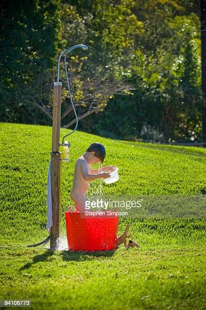 small boy bathes in backyard shower