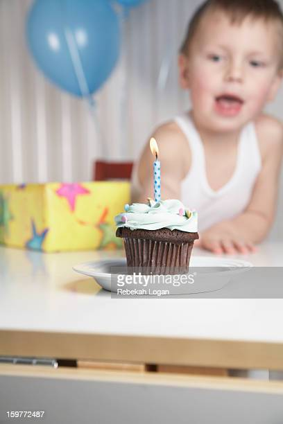 Small boy blowing out candle on cupcake.