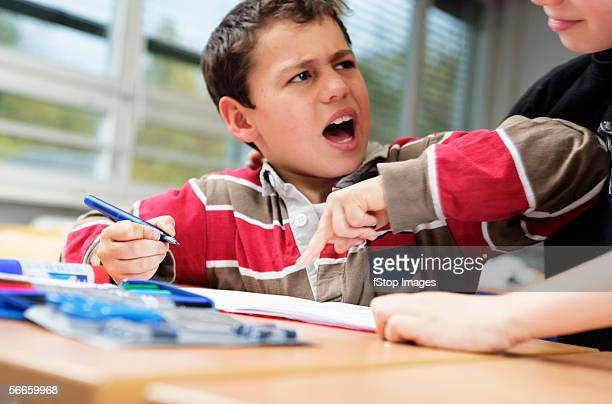 A small boy bothers his friend as he does his school work