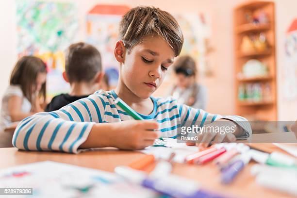 Petit garçon dessin dans une classe de maternelle.