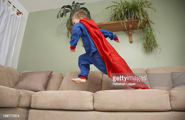 Small boy dressed as superhero jumping on couch.