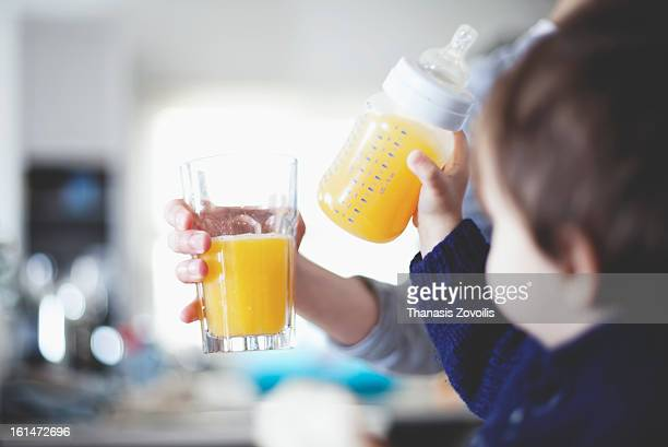 Small boy drinking orange juice