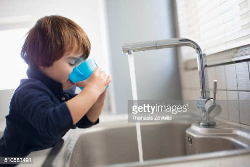 Small boy drinking water in the kitchen