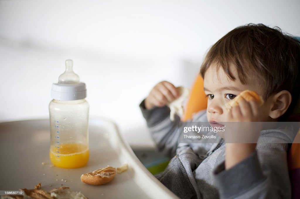 Small boy eating and drinking orange juice : Stock Photo