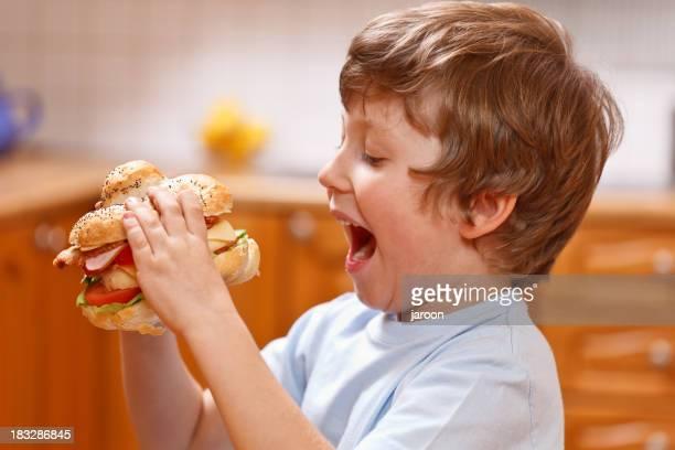 small boy eating big sandwich
