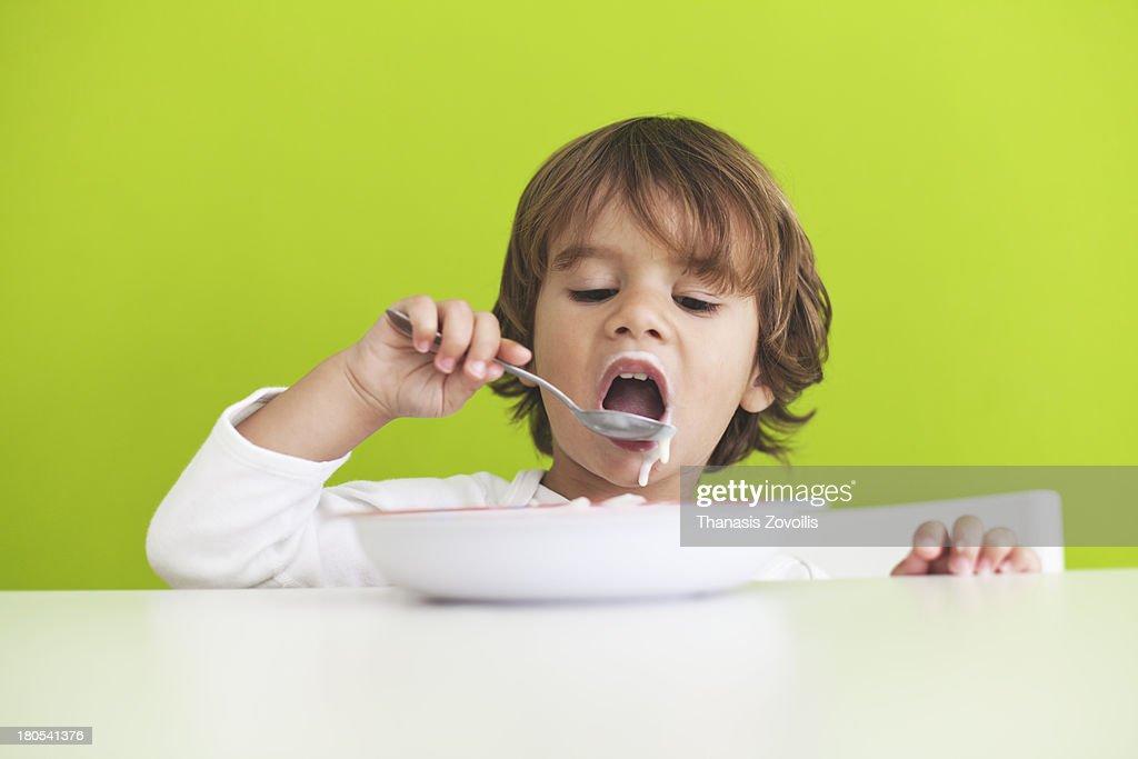 Small boy eating breakfast : Stock Photo