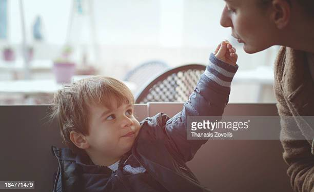 Small boy giving food to his mother