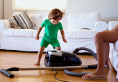 Small boy having fun with a vacuum cleaner