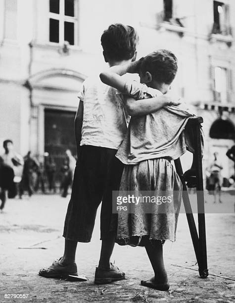 A small boy helps to support his disabled companion Naples August 1944