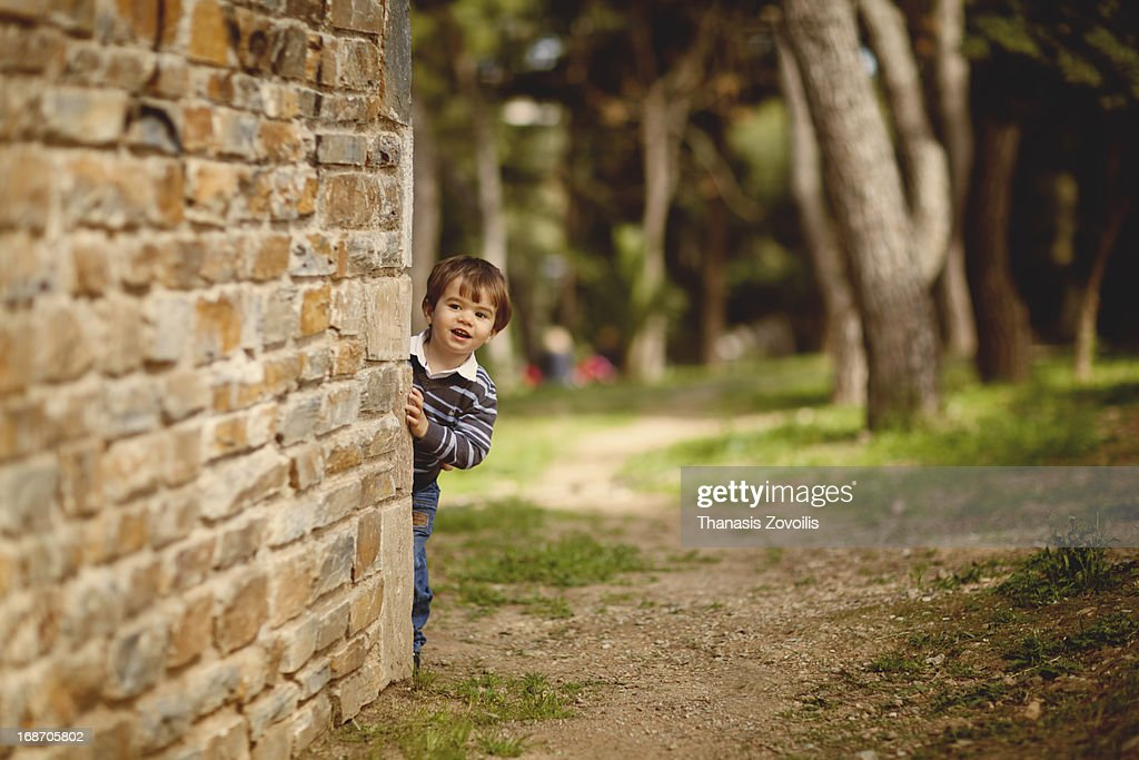 Small boy hidding behind a wall : Stock Photo