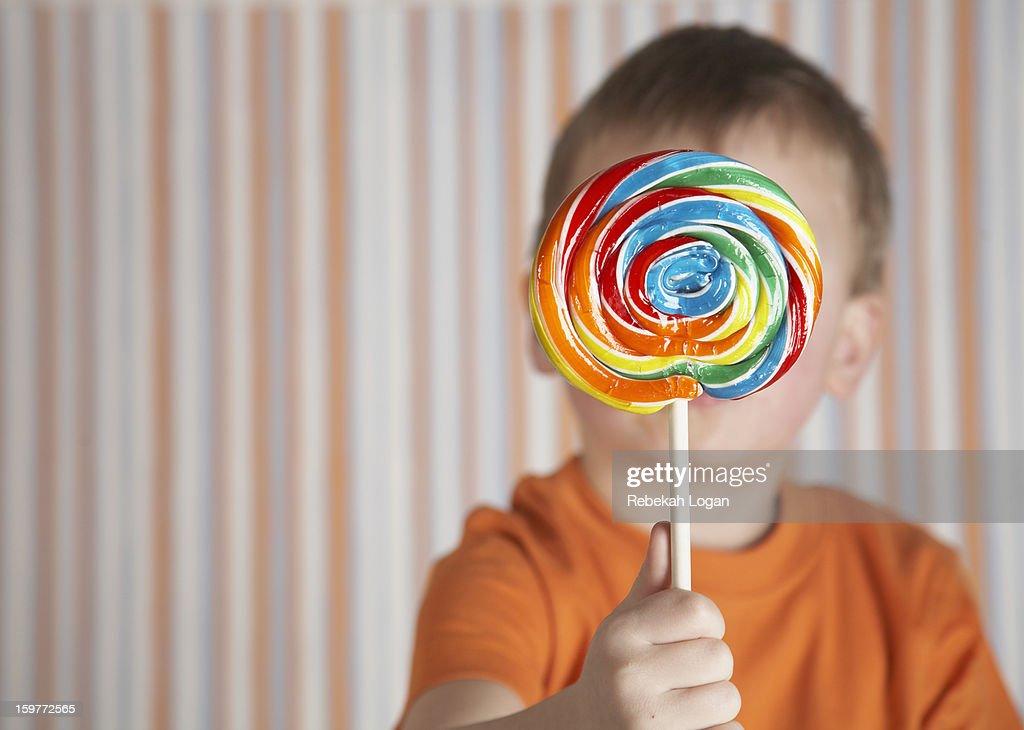 Small boy holding lollipop. : Stock Photo