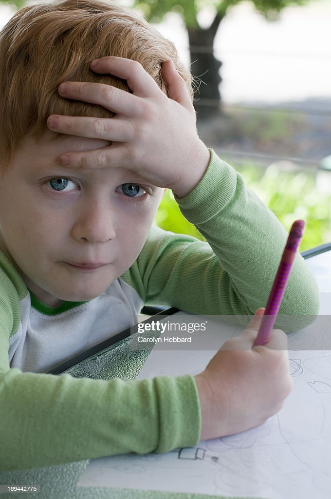 Small Boy Holding Pencil Looking Confused : Stock Photo