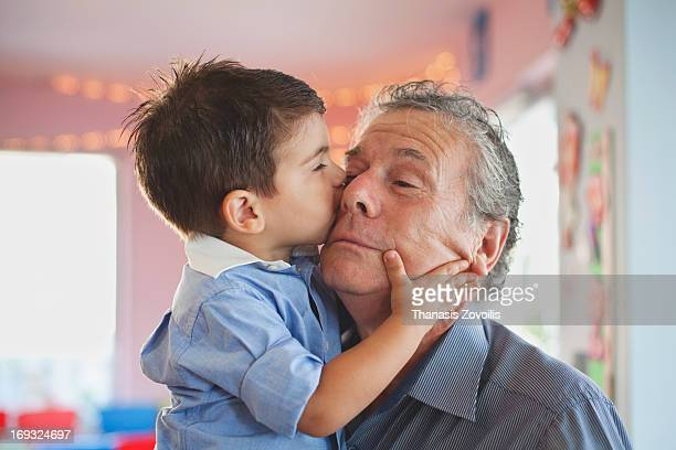 Small boy hugging his grandfather