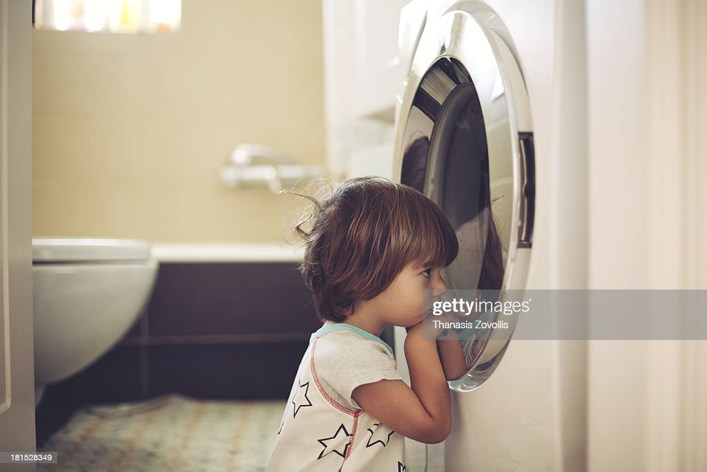Small boy in front of washing machine : Stock Photo