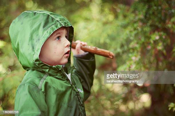 Small boy in rainy forest with rain coat