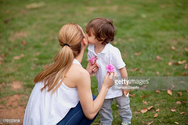 Small boy kissing his mother