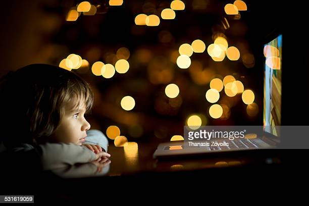 Small boy looking a laptop in the dark