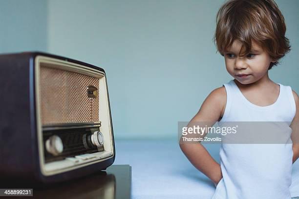 Small boy looking a vintage radio