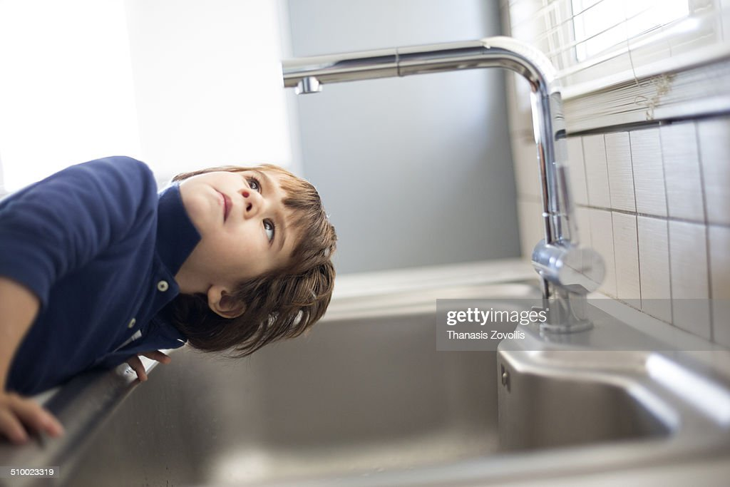 Small boy looking at faucet