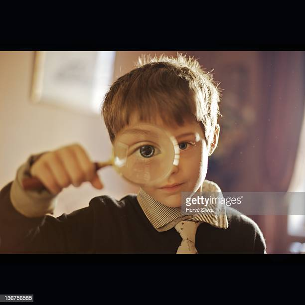 Small boy looking through magnifying glass