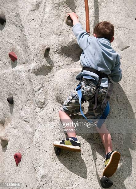 Small boy on climbing wall
