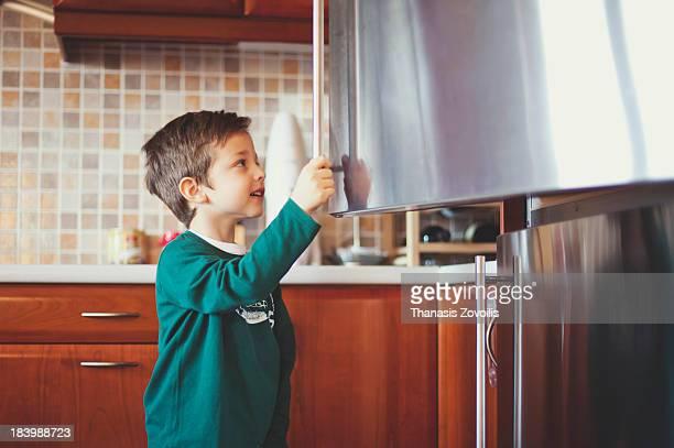 Small boy opening a refrigerator