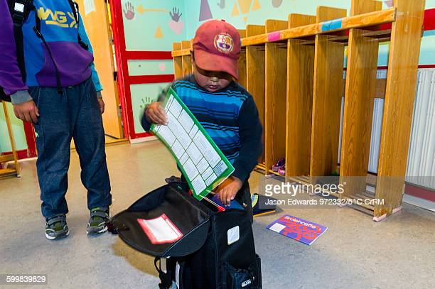 A small boy placing his books in a school bag at the end of the day Kangaamiut Gammel Sukkertoppen Qeqqata Municipality Greenland