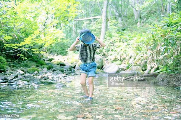 Small Boy Playing In A Stream