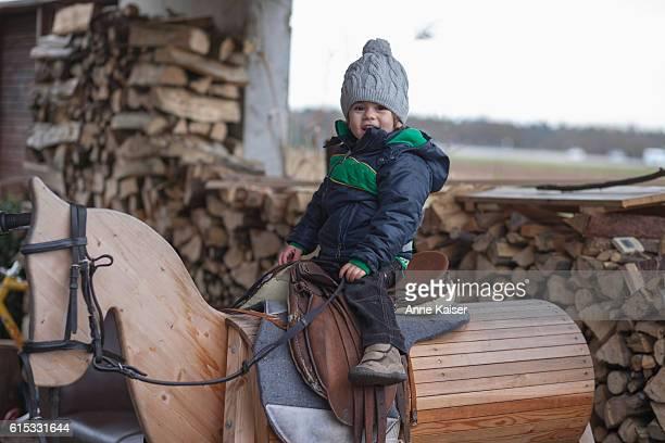 Small boy playing on wooden horse, Fürstenfeldbruck, Bavaria, Germany