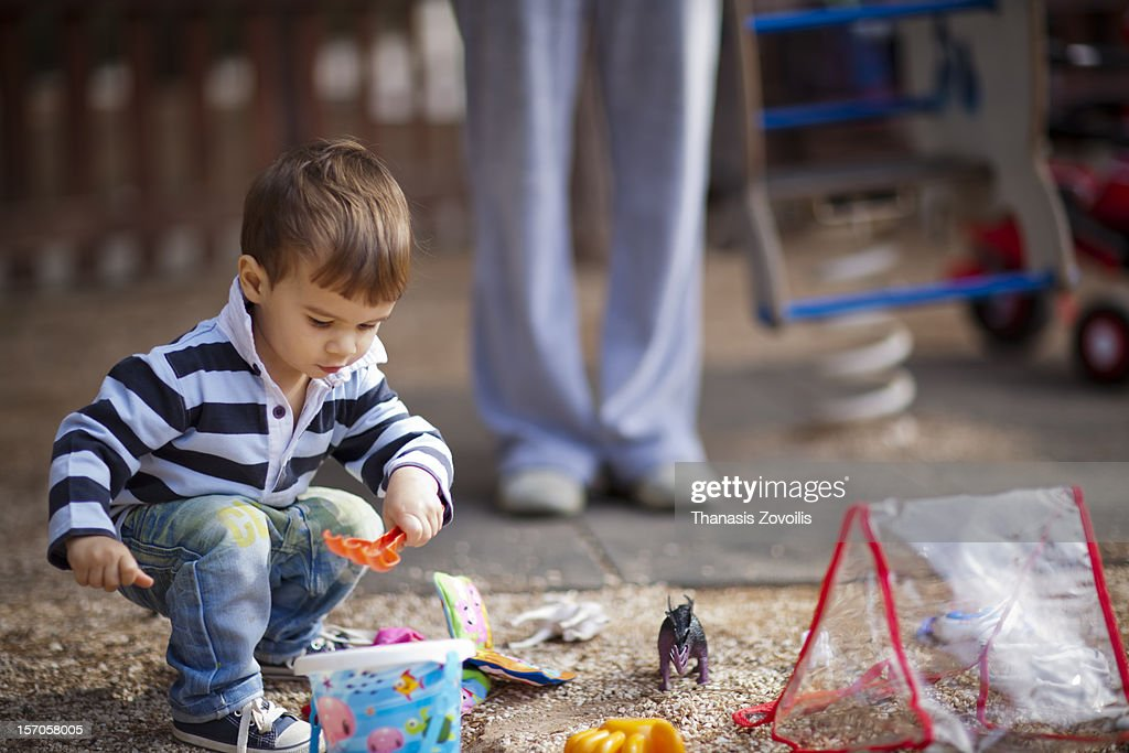 Small boy playing outside with his toys : Stock Photo