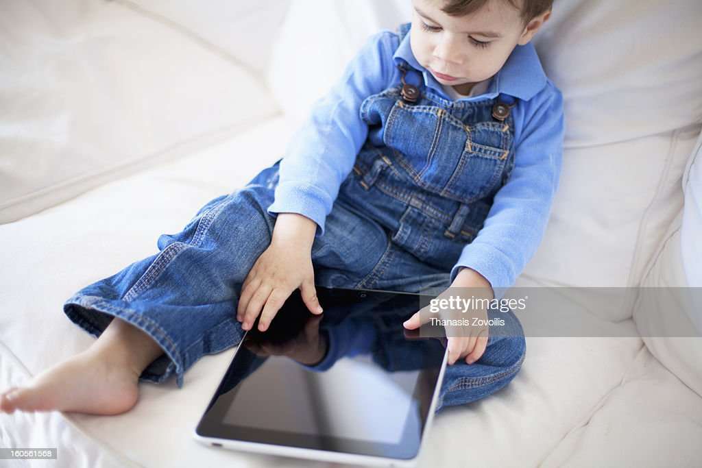 Small boy playing with a tablet : Stock Photo
