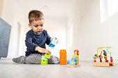 Small boy playing with little brick block toys at home on the floor